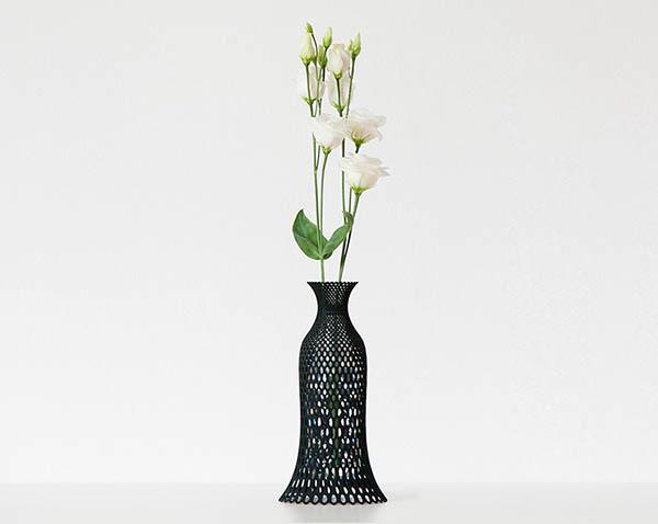 意大利设计师libero rutilo 近日推出了一款独特的花瓶作品,创造性地将3D打印与升级回收两种趋势结合在一起,为废旧塑料瓶创造出一种全新的用途。这款花瓶专为0.5升容量的废旧PET材质塑料水瓶及软饮瓶设计。全系列共包含四种不同的图案风格,都可以轻松将废旧塑料瓶通过瓶口旋转固定在其中。3D打印的结构包裹在透明塑料瓶外,将其隐藏在非常美观的几何网状结构下,形成若隐若现的独特效果。  3D打印花瓶可以轻松放置在塑料水瓶上方,并在瓶口处固定,从而在废旧物品的基础上创造出全新的用途。每种风格都展现出一种独特